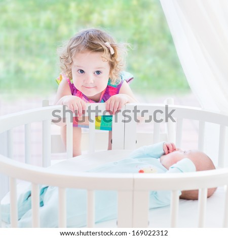 Cute toddler girl playing with her newborn baby brother in a white round bed next to a big window with garden view - stock photo