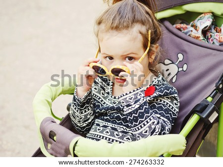cute toddler girl sitting in the stroller - stock photo