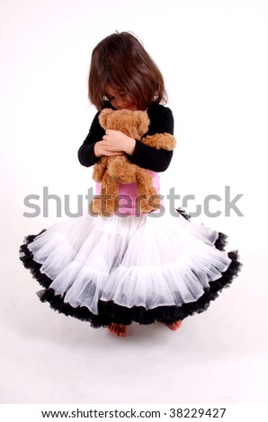 cute toddler girl wearing a frilly skirt cuddling a teddy bear - stock photo