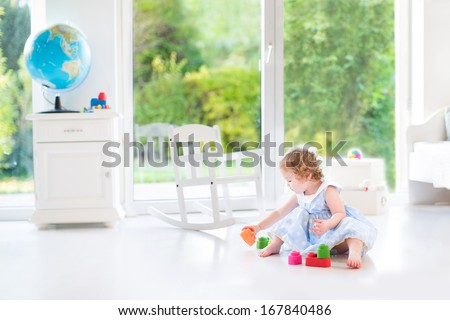 Cute toddler girl with curly hair wearing a blue dress playing in a white sunny bedroom with a big window with garden view  - stock photo