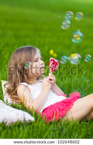Cute toddler girl with lollipop resting on the grass in summer day