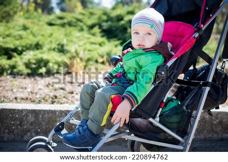 Cute Toddler in pram on a walk on a sunny day - stock photo