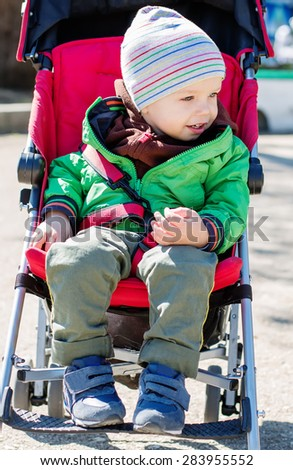 Cute Toddler in pram on a walk on a sunny day