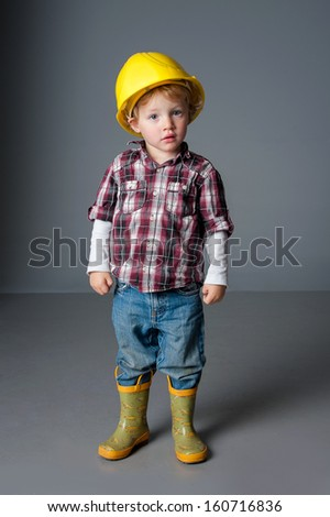 Cute toddler poses wearing fireman helmet and boots - stock photo
