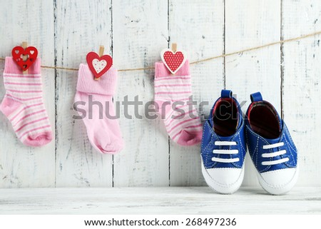 Cute toddler shoes and socks on wooden background - stock photo