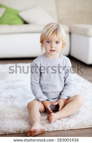 Cute toddler sitting on soft carpet at room - stock photo