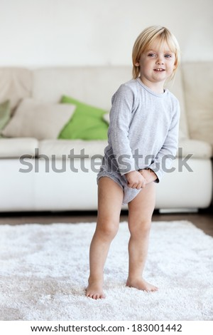 Cute toddler standing on soft carpet at room - stock photo