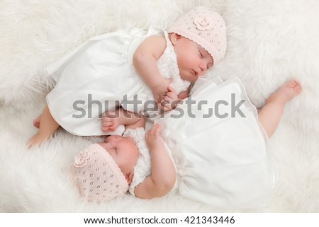 Cute twin sisters, newborn babies lying together. Wearing elegant white dresses - stock photo