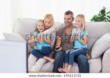 Cute twins and parents watching television sitting on a couch