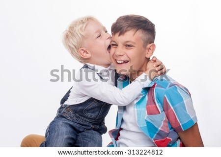 Cute two boys are playing and laughing. The elder boy is holding his little brother on knees. The small child is embracing and trying to bite male ear with joy. Isolated and copy space in left side - stock photo