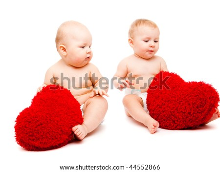 Cute valentine babies playing with red hearts - stock photo