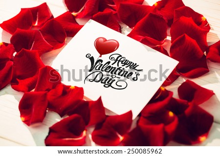 Cute valentines message against card surrounded by rose petals