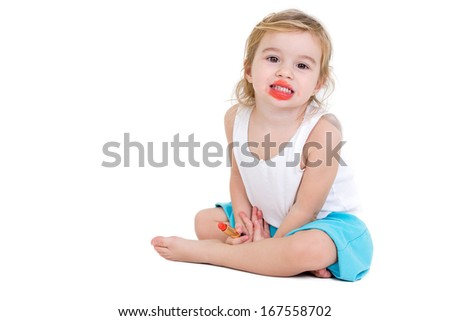 Cute very young girl practising to be a fashion model sitting on the floor grinning at the camera with her mouth smeared with bright red lipstick which she is holding in her hand, on white