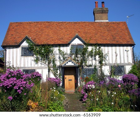 Cute whitewashed timbered medieval cottage in a rural English village - stock photo