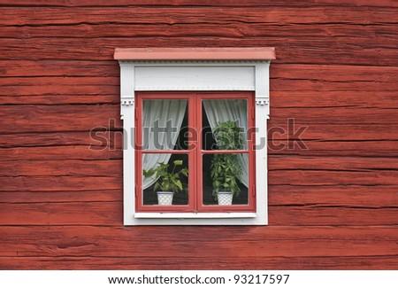 Cute window on red swedish house wall - stock photo