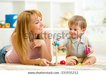 cute woman and kid play together indoor - stock photo
