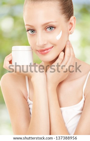 Cute woman applying cream to her face - stock photo