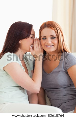 Cute woman being told a secret in a living room