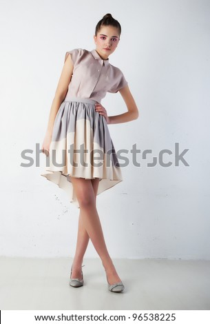 Cute Woman Fashion Model in Gorgeous Light Dress posing in studio - Sales and Shopping Concept - stock photo