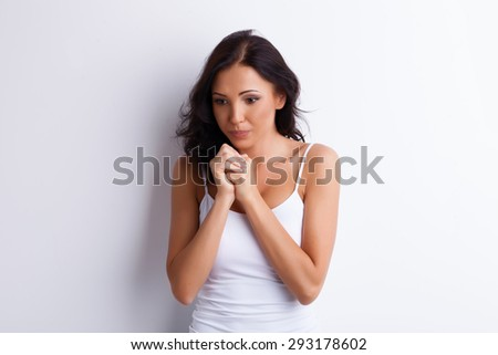 Cute woman has fear. She is compressed and frightened. Her hands are joined together. Isolated and there is copy space in left and right side - stock photo