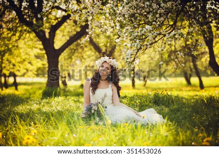 cute woman in a dress and a wreath sitting on the grass in a lush garden - stock photo