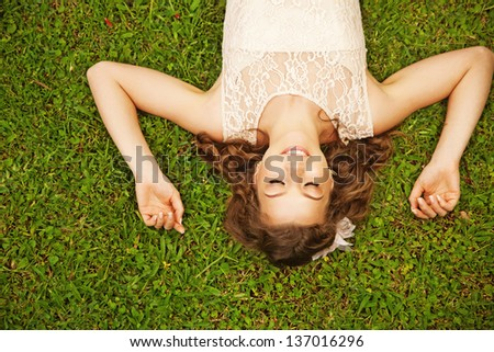 cute woman lying on the grass - stock photo
