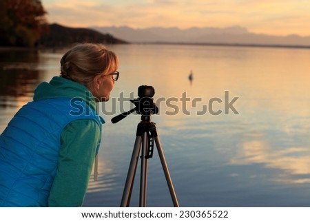 Cute woman movie sunset with swans on lake, horizontal - stock photo