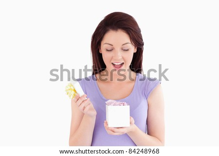 Cute woman opening a box in a studio