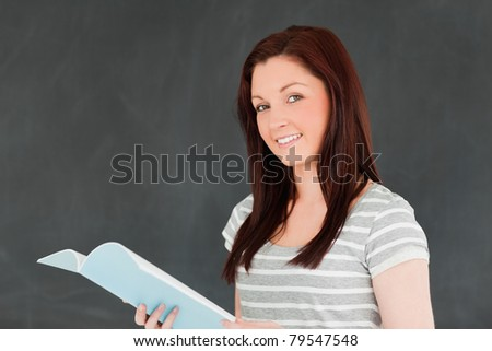 Cute woman reading her notes in front of a blackboard in a classroom