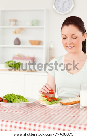 Cute woman ready to eat a sandwich for lunch in her kitchen