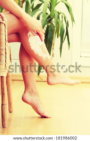 Cute woman shaving her legs at home - stock photo
