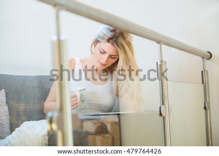 cute woman touching screen of tablet computer while seated in dark gray sofa chair
