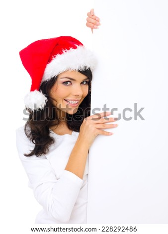 Cute woman wearing a Santa hat holding the side of a blank white sign with copyspace for your seasonal advertising or greeting - stock photo