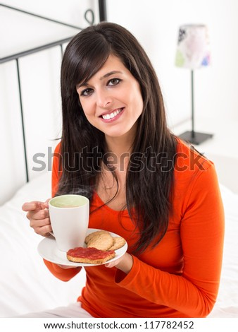 Cute woman with breakfast drinking steaming coffee and holding a plate with biscuits and toast with jam in bedroom. - stock photo