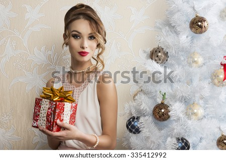 cute woman with elegant style and pearl necklace posing with make-up and hair-style near decorated christmas tree and taking gift box in the hand