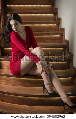 cute woman with long black hair, sexy short red dress and heels, sitting on elegant wood stairs in fashion pose