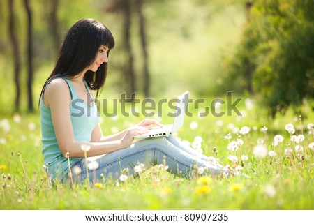 Cute woman with white laptop in the park with dandelions - stock photo