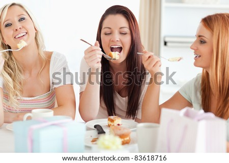 Cute Women sitting at a table eating a cake in a kitchen - stock photo