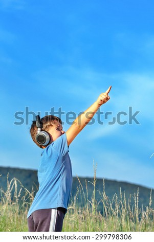 Cute 6 year old boy listening to music on headphones in nature