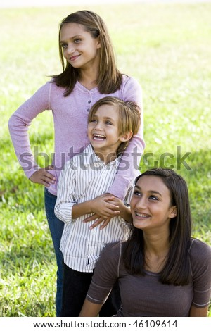 Cute 5 year old boy with two older sisters together outdoors on sunny day - stock photo