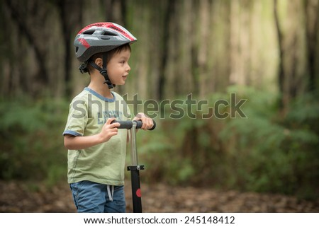 Cute 4 year old mixed race Asian Caucasian boy plays on his scooter on a forest road - stock photo