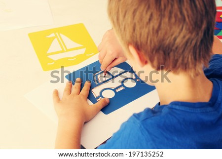 cute 6 years old boy drawing - stock photo