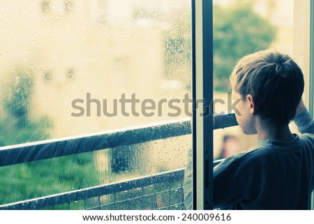 Cute 6 years old boy looking at the rain - stock photo