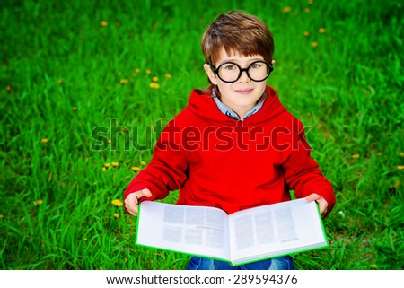 Cute 7 years old boy sitting on a grass and reading a book. Summer day.  - stock photo