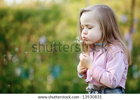 Cute 5 years old girl blowing dandelion on nice summer afternoon