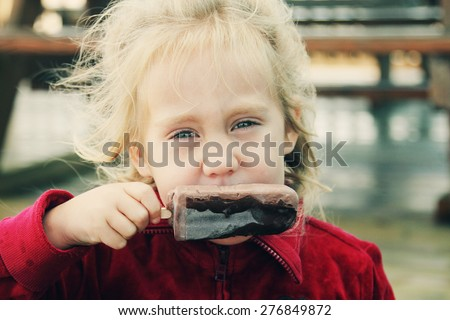 cute 4 years old girl eating ice cream - stock photo