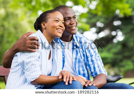 cute young african american couple daydreaming in forest - stock photo