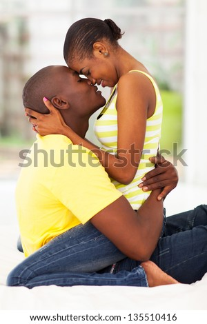 cute young african american couple kissing in bed - stock photo