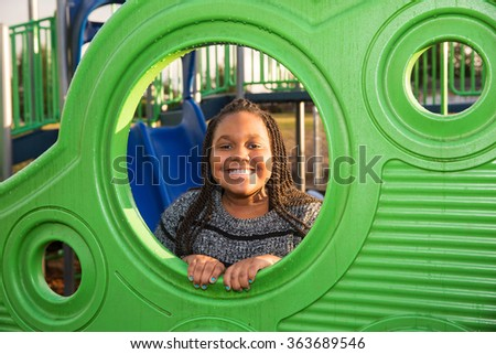 Cute young African American girl playing outside at school playground - stock photo