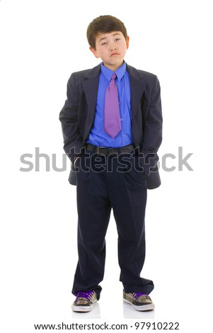 Cute young asian boy in suit and tie and hands in his pockets deep in thought isolated on white background